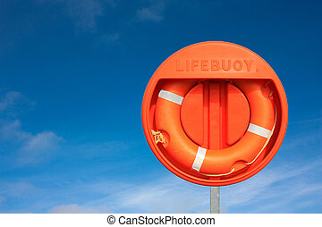 Orange lifebuoy against a blue sky