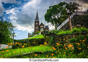 Orange lillies and St. Peters Roman Catholic Church, in...