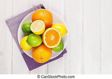 Orange, lime and lemon. Citrus fruits on white wooden table. Top view with copy space