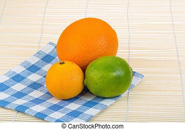 Orange, lime, tangerine heap on the wood background