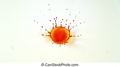 Orange Liquid falling into Water against White Background, Slow motion
