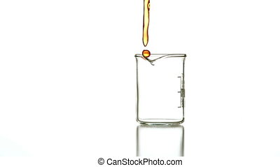 Orange liquid pouring into glass beaker