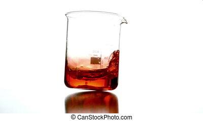 Orange liquid swirling in beaker