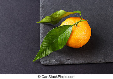Orange mandarin on the black slate stone background