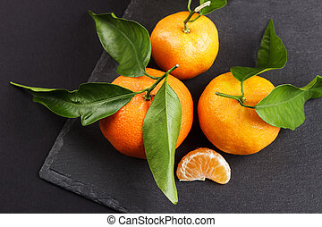 Orange mandarins on the black slate stone background