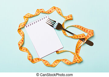 Orange measure tape, open notebook and fork on blue background with empty space for your idea. Top view of healthy lifestyle concept