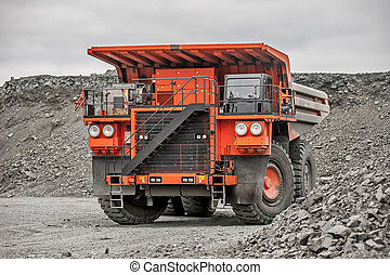 Orange mining vehicle driving in the pit