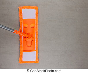 orange MOP on grey tile background with copy space, top view close up