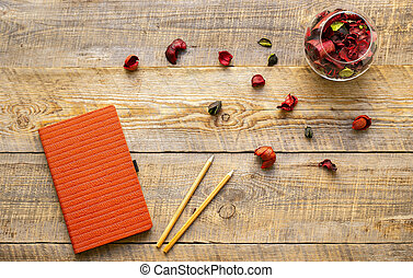 orange notebook with flower on wooden table