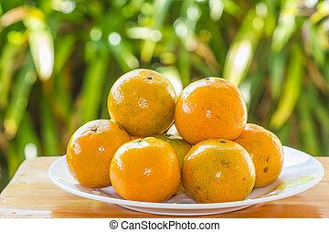 Orange on dish on wooden table