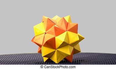 Orange origami sharp ball exposition. Polygon shape form...