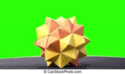 Orange origami spiky ball exposition. Green hromakey...