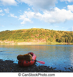 Orange packraft rubber boat with backpack on a river
