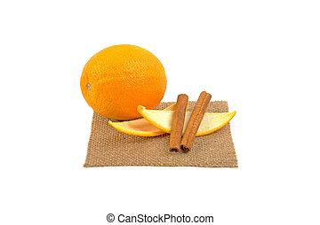 orange peas with lobules two cinnamon sticks on burlap on white background