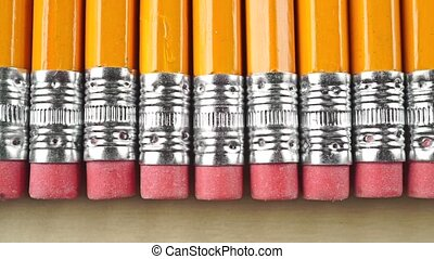 Orange pencils with pink erasers, macro dolly shot. Total...