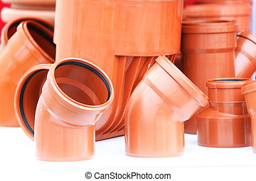 orange pieces- set of brown drain pipes from PVC on white background
