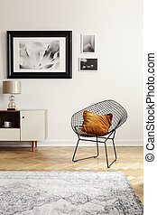 Orange pillow on a black, industrial net chair by a white wall with gallery of mock-up pictures in an elegant living room interior.