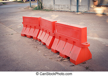 Orange plastic barrier lined up on the road