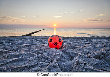 orange plastic soccer ball at the beach with sunset