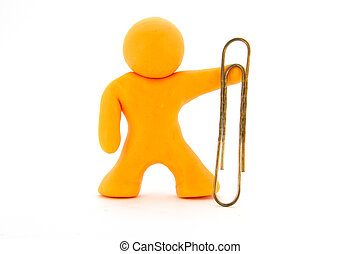 Orange plasticine character and big paperclip. Stationery. Isolated over white background