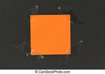 orange post-it stuck to a blackboard with tape