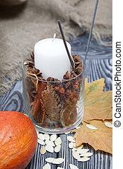 Orange pumpkin, seeds and candle. Nearby are dried maple leaves. On brushed pine boards painted black and white.