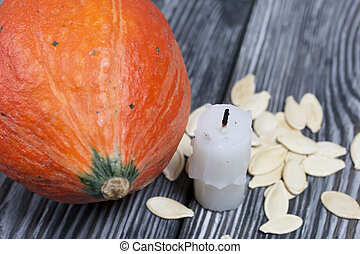 Orange pumpkin, seeds and candle stub. On brushed pine boards painted black and white.