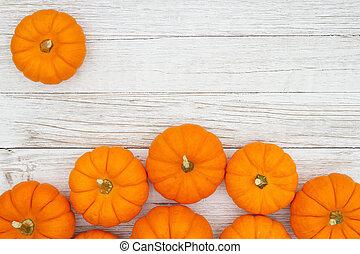Orange pumpkins on weathered whitewash wood textured background
