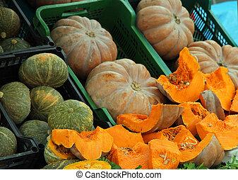 orange PUMPKINS sold at stalls in the vegetable market