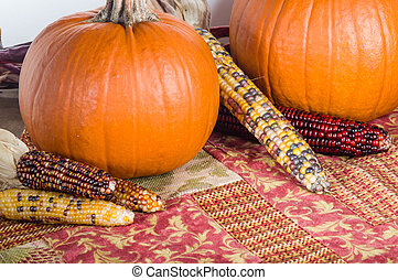 Orange pumpkins with colorful ears of corn