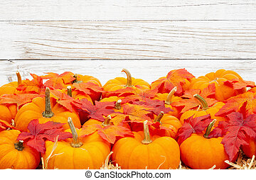 Orange pumpkins with fall leaves on straw hay with weathered whitewashed textured wood