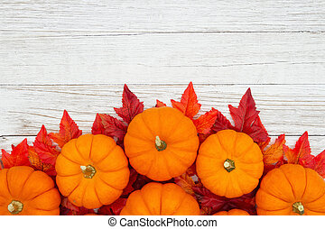 Orange pumpkins with fall leaves on weathered whitewash wood textured background