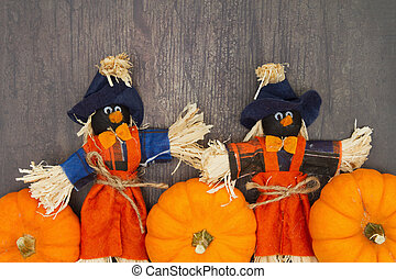 Orange pumpkins with fall scarecrows on weathered brown grunge wood textured background