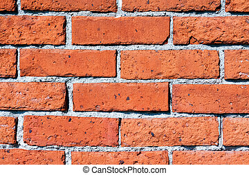 An old wall is constructed of orange red clay bricks showing a rustic and worn texture.