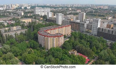 Orange residential building J shaped aerial drone view right side flying around camera movement