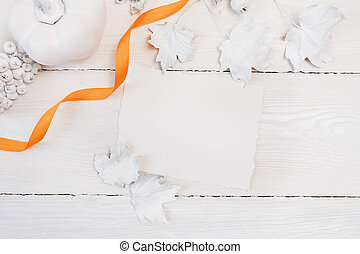 orange ribbon, white pumpkin, berries and leaves on a wooden mockup autumn background. Greeting card for Thanksgiving Day in rustic style with space for your text. Flat lay. Top view