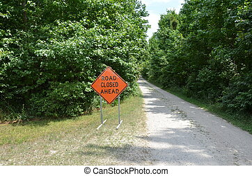 orange road closed sign with path or trail