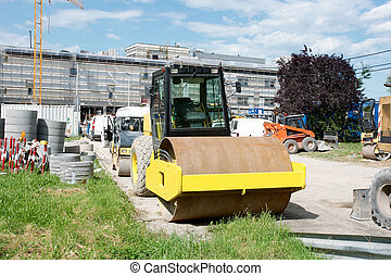 Orange road-roller at construction site