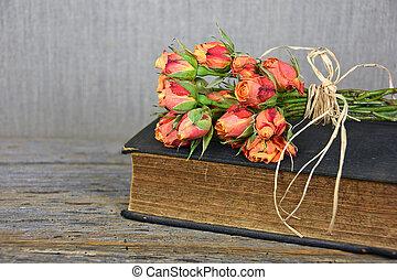 orange rose bouquet on book