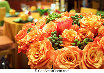 Orange roses in a lush bouquet in a wedding reception venue