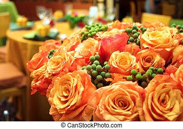 Orange roses in a lush bouquet in a wedding reception venue