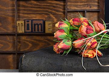 orange roses on old book with wood letterpress