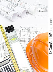Orange safety helmet and rolled project drawings