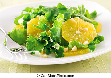 Fresh salad leaves with orange and pine nuts