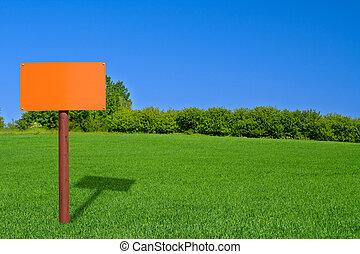 orange sign post on beautiful green meadow
