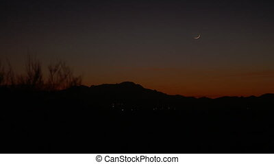 Orange Sky And Crescent Moon Over Mountains - Steady, wide...