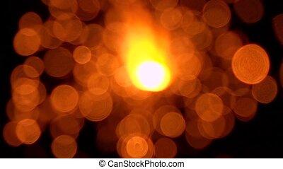 Orange sparkler against dark background, bokeh video. Super...