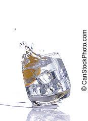 orange splashing into glass of water on white background