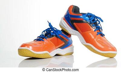 Orange sport badminton shoes rotating over white background