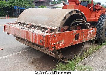 Orange steamroller on the road.